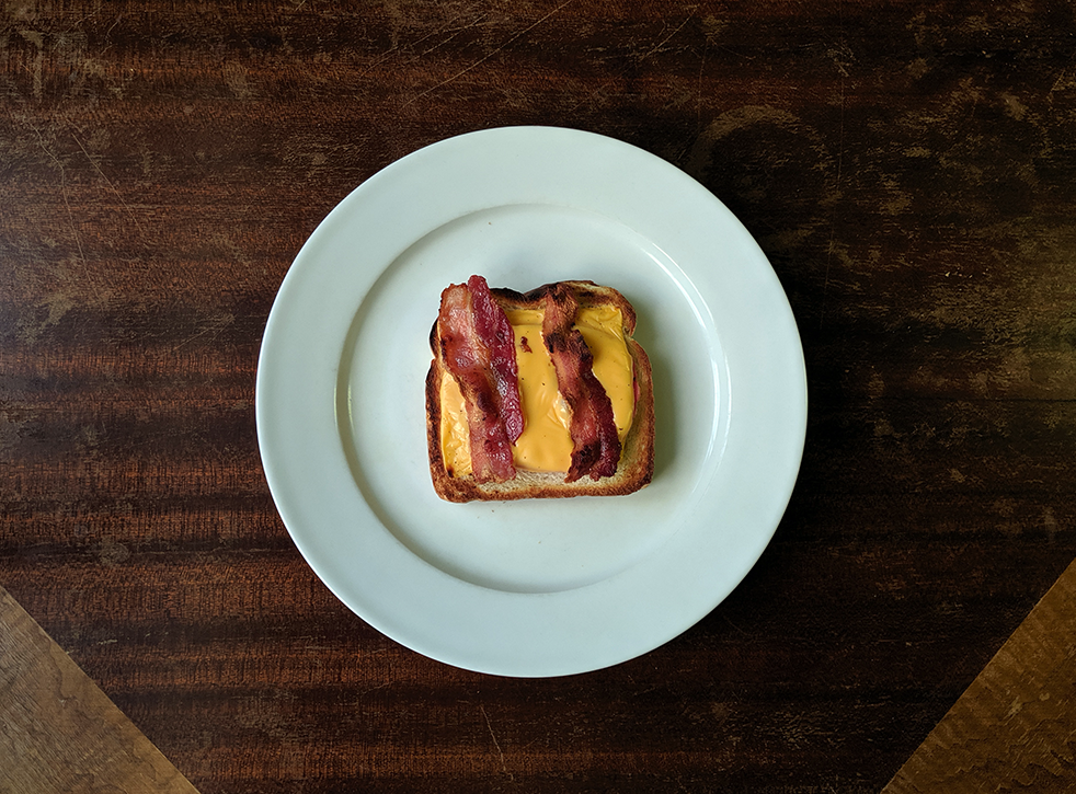 a wooden table with a white plate holding a slice of toast topped with american cheese and bacon