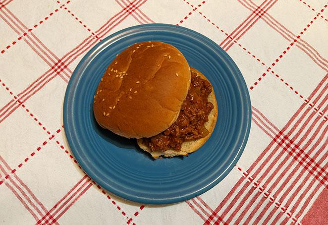 a sloppy joe sandwich on a blue plate