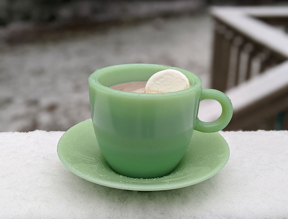 a green cup of hot chocolate and a marshmallow sitting in front of a snowy background