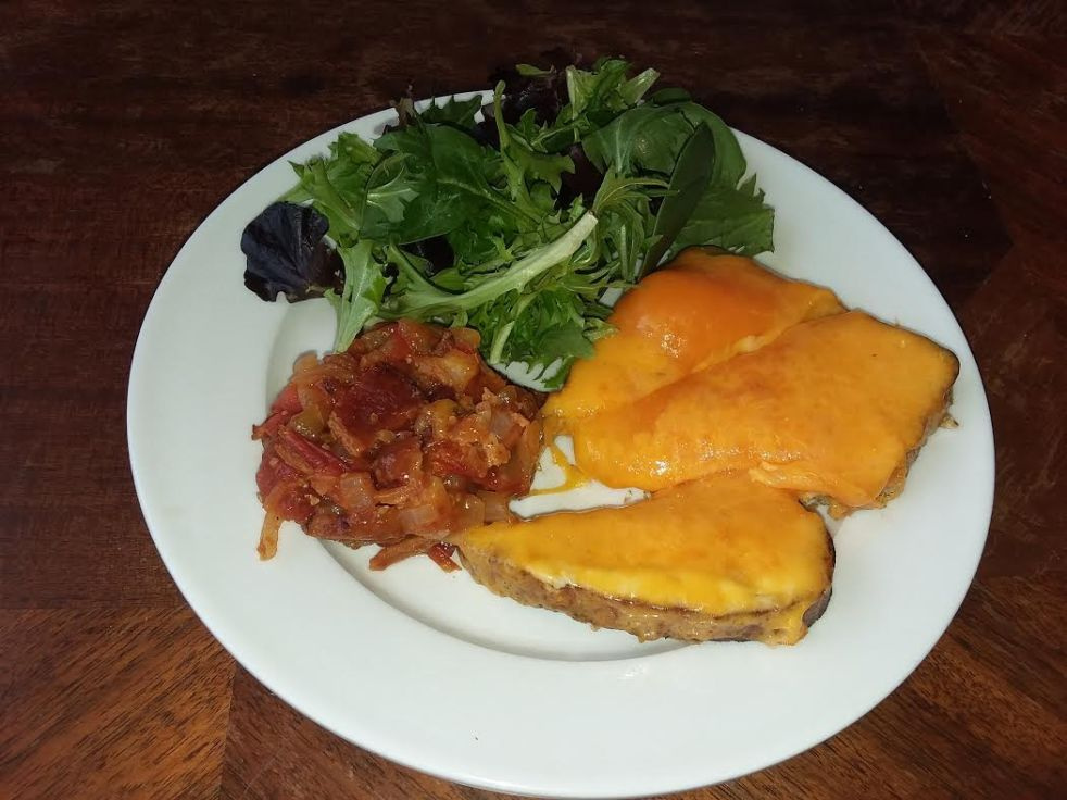 an open-faced cheddar and horseradish sandwich with tomato-bacon jam and a side salad