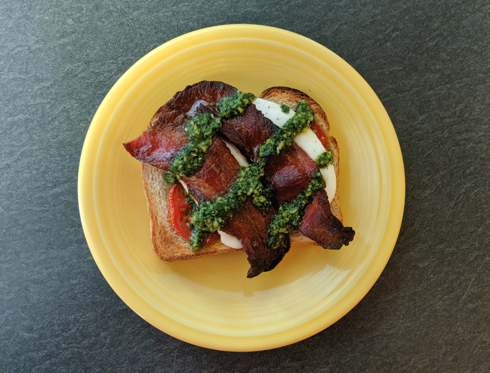 a piece of toast topped with roasted tomato, mozzarella cheese, and bacon on a yellow plate