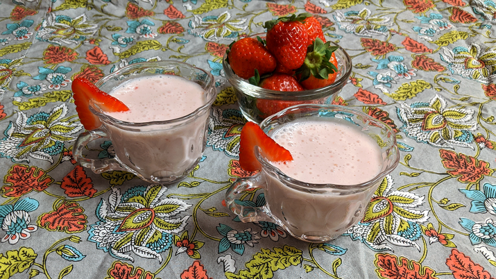two small glass cups of pink milk punch garnished with strawberries