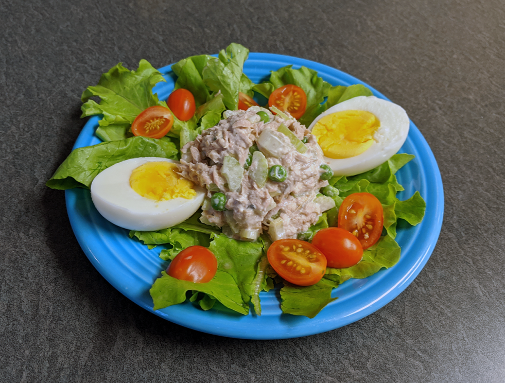 a scoop of tuna salad on a bed of leaves with egg and chopped tomato