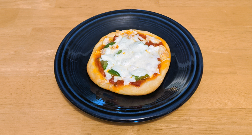 a mini pizza on a dark blue plate