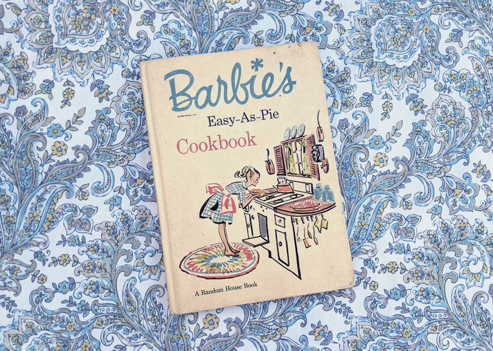 a vintage copy of Barbie's Easy-As-Pie Cookbook on a bright paisley tablecloth