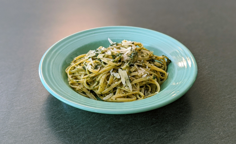 spaghetti with pesto sauce and cheese in a shallow teal bowl